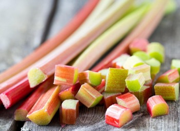 freshly cut pieces of rhubarb on wooden surface