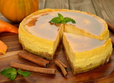 Pumpkin cheesecake with caramel icing on brown background